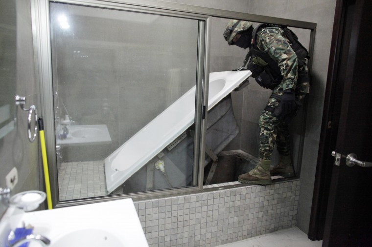"A Mexican marine lifts a bathtub that leads to a tunnel and exits in the city's drainage system at one of the houses of Joaquin ""Chapo"" Guzman in Culiacan, in this February 27, 2014 file photo. REUTERS/Daniel Becerril"