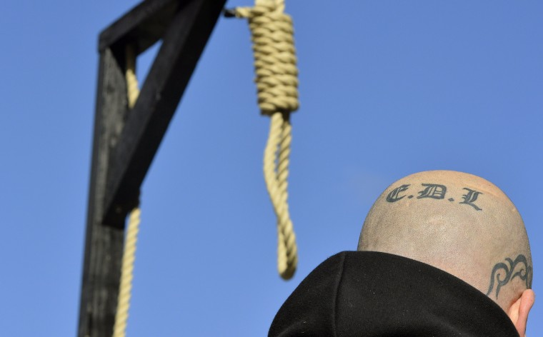A supporter of the English Defence League with a tattoo on his head stands by a replica hangman's noose and gallows during a protest outside the Old Bailey courthouse in London, in this February 26, 2014 file photo. REUTERS/Toby Melville