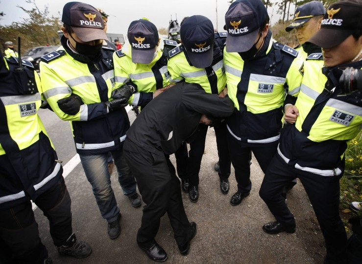 A family member of a passenger missing after the South Korean Sewol ferry capsized is blocked by police during a protest in Jindo calling for a meeting with South Korean President Park Geun-hye and demanding the search and rescue operation be speeded up, in this April 20, 2014 file photo. REUTERS/Kim Kyung-Hoon