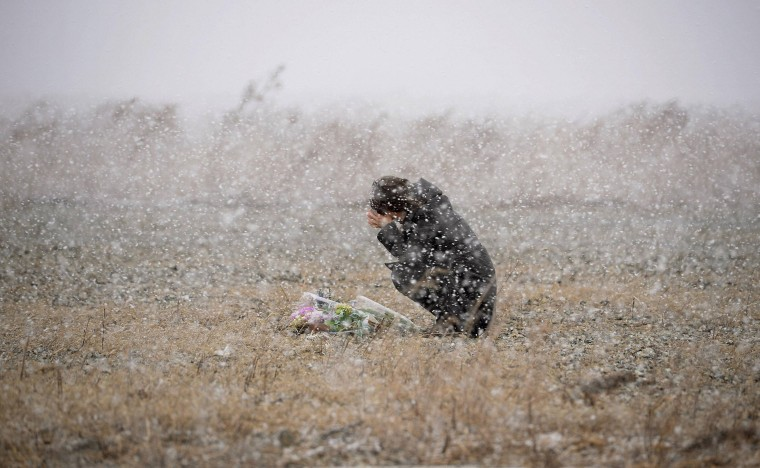A woman prays for the deceased of the March 11, 2011 earthquake and tsunami, as snow falls, at a place where she was employed at a photo studio at the time, in Rikuzentakata, Iwate prefecture, in this file photo taken by Kyodo March 11, 2014. Mandatory credit REUTERS/Kyodo