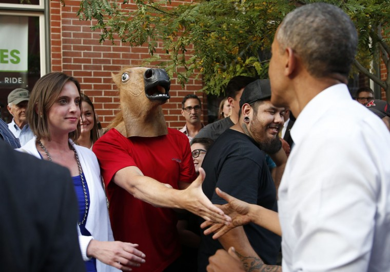 U.S. President Barack Obama greets a man wearing a horse mask during a walkabout in Denver in this July 8, 2014 file photo. REUTERS/Kevin Lamarque/Files