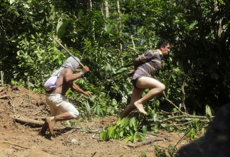 A Ka'apor Indian warrior (L) chases a logger who tried to escape after he was captured during a jungle expedition to search for and expel loggers from the Alto Turiacu Indian territory, near the Centro do Guilherme municipality in the northeast of Maranhao state in the Amazon basin, in this August 7, 2014 file photo. REUTERS/Lunae Parracho/Files