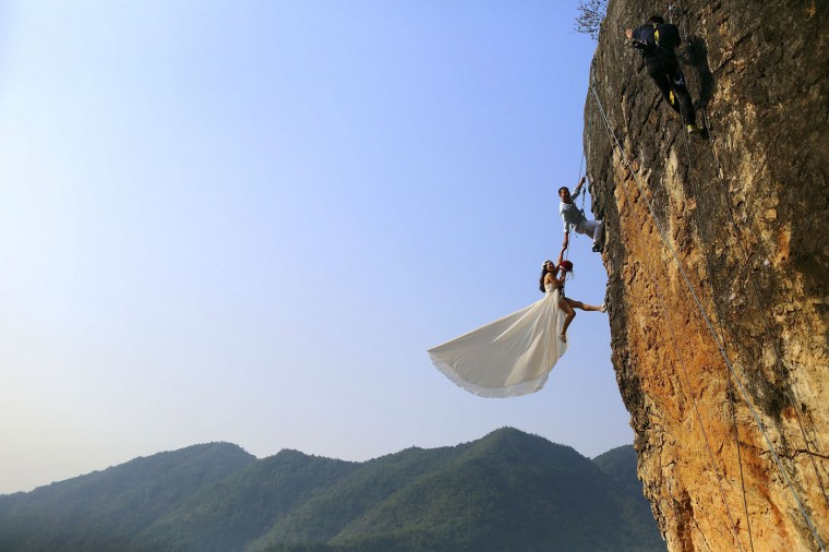 Zheng Feng, an amateur climber takes wedding pictures with his bride on a cliff in Jinhua, Zhejiang province, in this October 26, 2014 file photo. REUTERS/China Daily/Files