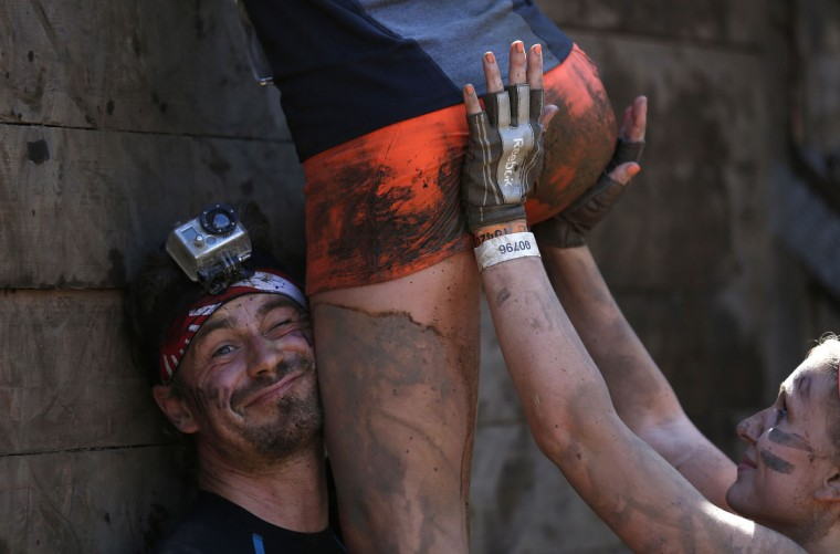 "Participants climb over a wall at the ""Tough Mudder"" endurance event series in Arnsberg in this September 6, 2014 file photo. REUTERS/Ina Fassbender/Files"
