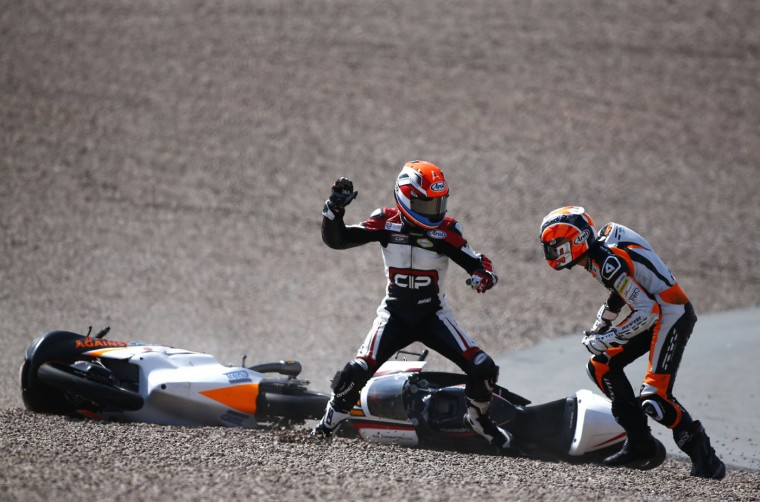 Mahindra Moto3 rider Bryan Schouten of the Netherlands fights with compatriot Kalex KTM Moto3 rider Scott Deroue (R) after they crashed during the German Grand Prix at the Sachsenring circuit in the eastern German town of Hohenstein-Ernstthal, in this July 13, 2014 file photo. REUTERS/Thomas Peter/Files