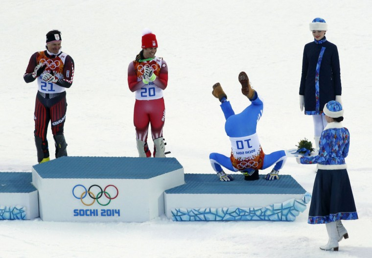 Third-placed Italy's Christof Innerhofer (2nd R) does a somersault on the podium as winner Switzerland's Sandro Viletta (2nd L) and second-placed Croatia's Ivica Kostelic (L) laugh after the men's alpine skiing super combined event at the 2014 Sochi Winter Olympics at the Rosa Khutor Alpine Center in this February 14, 2014 file photo. REUTERS/Stefano Rellandini/Files