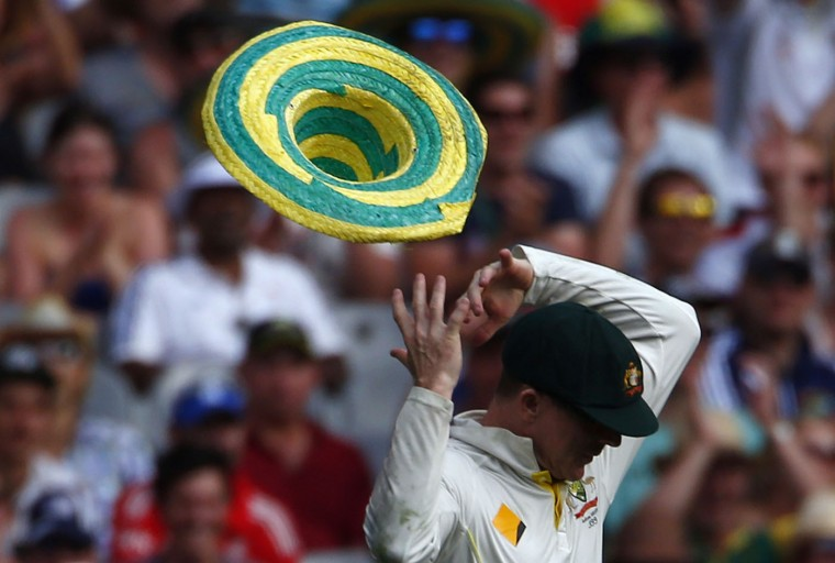 A hat that blew onto the field, is blown off the head of Australia's Chris Rogers after he put it on during the first day of the fourth Ashes cricket test against England, at the Melbourne cricket ground, in this December 26, 2013 file photo. REUTERS/David Gray/Files