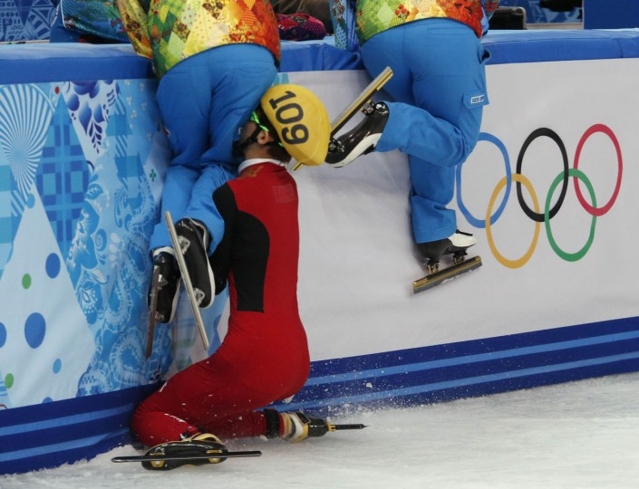 Olympic officials who maintain the ice jump out of the way as China's Kexin Fan crashes out into the barrier in the women's 500 metres short track speed skating semifinal event at the Iceberg Skating Palace during the 2014 Sochi Winter Olympics in this February 13, 2014 file photo. REUTERS/David Gray/Files