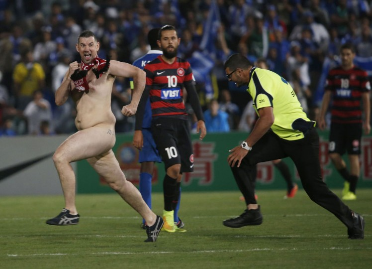 A streaker runs across the pitch as a security guard prepares to tackle him during the Asian Champions League final first-leg soccer match between Australia's Western Sydney Wanderers and Saudi Arabia's Al Hilal at Parramatta Stadium in Sydney in this October 25, 2014 file photo. REUTERS/Jason Reed/Files