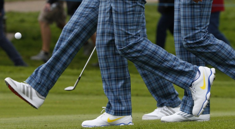 European Ryder Cup player Martin Kaymer (L) kicks his ball as he walks with teammates Rory McIlroy (C) and Sergio Garcia along the seventh fairway during practice ahead of the 2014 Ryder Cup at Gleneagles in Scotland in this September 23, 2014 file photo. REUTERS/Russell Cheyne/Files