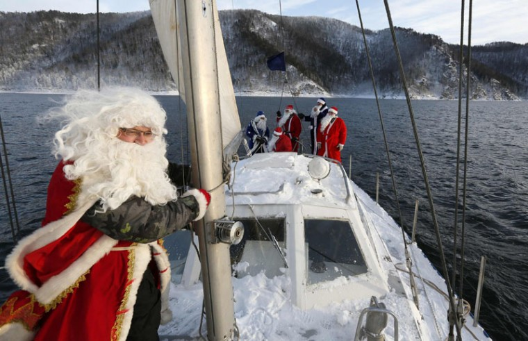 "Members of the ""Skipper"" yacht club dressed as Father Frost, the Russian equivalent of Santa Claus, sail a yacht to mark the end of the sailboat season, with the air temperature at about minus 18 degrees Celsius (minus 0.4 degrees Fahrenheit), on the Yenisei River, outside Russia's Siberian city of Krasnoyarsk,. (Ilya Naymushin/Reuters)"