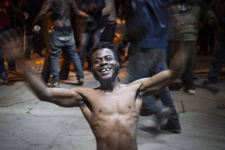 An African migrant reacts upon arriving at CETI, the short-stay immigrant centre, after crossing the border from Morocco to Spain's North African enclave of Melilla December 31, 2014. More than 50 migrants managed to pass the border fence and are currently held at CETI, local authorities said. (Jesus Blasco de Avellaneda/Reuters photo)