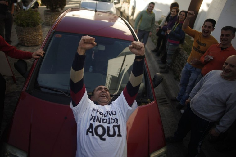 "A lottery seller celebrates after selling lottery tickets with a winning number of Spain's Christmas Lottery ""El Gordo"", as he celebrates with winners in El Gastor, near Cadiz, December 22, 2014. The total prize money of 2.4 billion euros is split into thousands of cash prizes amongst hundreds of winning numbers. (Jon Nazca/Reuters)"