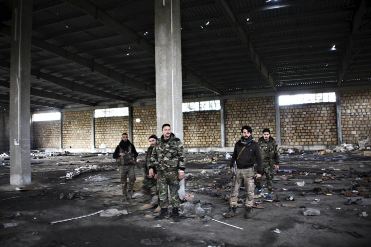Forces of Syria's President Bashar al-Assad stand in a damaged factory in the Handarat area after regaining control of the whole area, they said, north of Aleppo December 31, 2014. (George Ourfalian/Reuters photo)