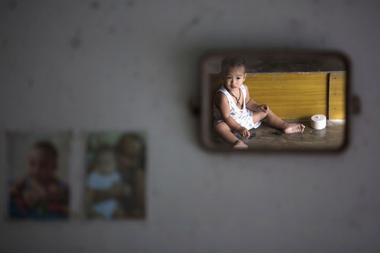 A child is reflected in a mirror at barber's home in Ban Nam Khem, December 13, 2014. Therasak, a local barber who survived 2004 tsunami with his family members, returned to the village soon after disaster but says his 22 year old daughter still suffers from tsunami related illness. Ban Nam Khem, a small fishing village on Thailand's Andaman Sea coast and home to a large migrant workers' community, lost nearly half of its 5,000 population in the tsunami.