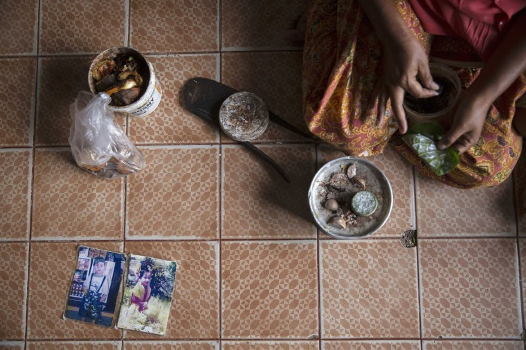 Manee, the 45-year-old wife of an unemployed fisherman from Myanmar, prepares betel nuts after showing pictures of her children killed in the 2004 tsunami at her home in Ban Nam Khem, December 13, 2014. Manee lost all her three children aged three, four and nine when tsunami hit a small fishing village on Thailand's Andaman Sea coast on December 26, 2004. Following the disaster, she and her husband returned to Myanmar but came back to Ban Nam Khem few years after looking for a job. They have two children now.
