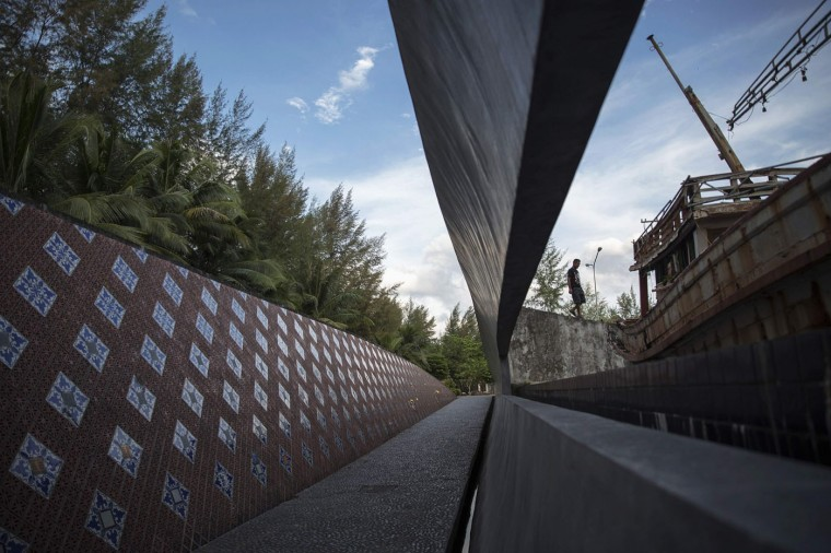 A visitor walks on a wave-shaped tsunami monument in Ban Nam Khem, December 13, 2014. Ban Nam Khem, a small fishing village on Thailand's Andaman Sea coast and home to a large migrant workers' community, lost nearly half of its 5,000 population in the tsunami.