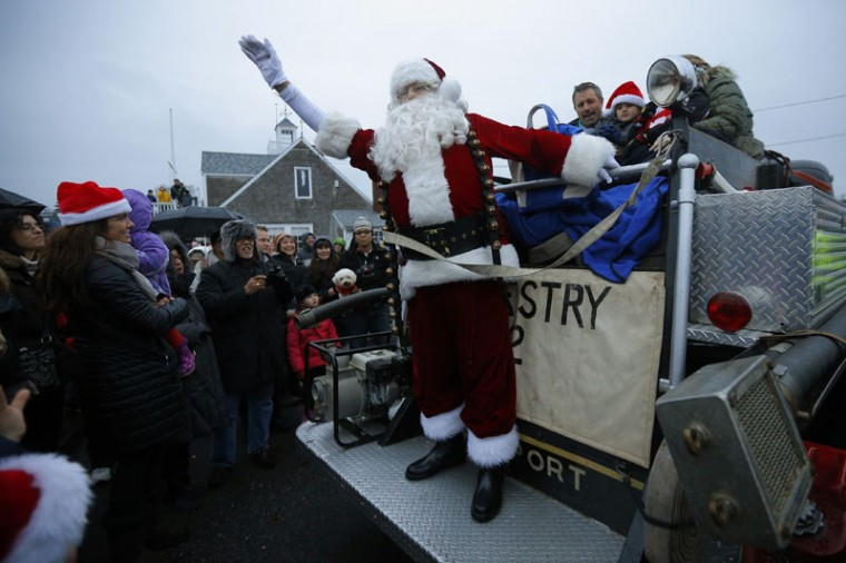 A man dressed as Santa Claus waves from the back of an antique fire truck after arriving on a lobster boat for the town's Tree Lighting ceremony in Rockport, Massachusetts December 6, 2014. (Brian Snyder/Reuters)