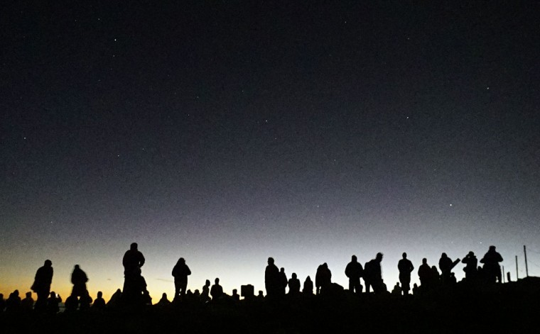 Visitors gather to watch the sunrise on the 10,023 feet (3,055 meters) summit of the Haleakala volcano on the Hawaiian island of Maui December 15, 2014. (REUTERS/Bob Strong)