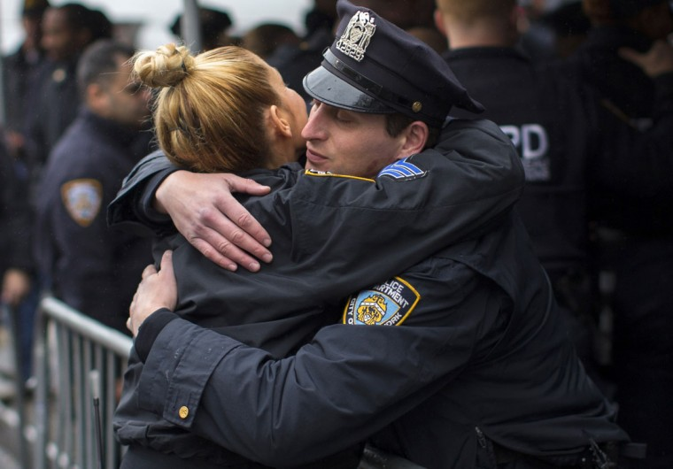 New York City Police officers embrace as they visit a makeshift memorial at the site where two of their fellow police officers were fatally shot in the Brooklyn borough of New York, December 23, 2014. NYPD officers, Wenjian Liu and Rafael Ramos were shot and killed as they sat in a marked squad car in Brooklyn on Saturday afternoon, New York Police Commissioner William Bratton said. The suspect in the shooting then shot and killed himself, according to Bratton. (REUTERS/Mike Segar)