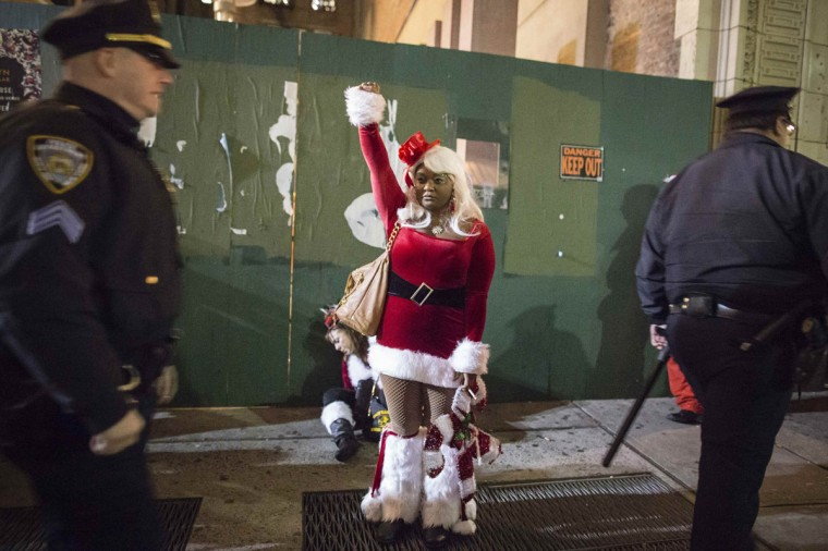 A woman gestures as she blocks a drunken reveler from police while taking part in SantaCon through Midtown Manhattan, New York December 13, 2014. Waves of revelers dressed in Santa Claus outfits invaded Midtown Manhattan on Saturday as part of New York's version of SantaCon, a massive pub crawl that organizers scaled back this year in part to prevent conflicts with a nearby protest march. The loosely organized event, which moves every year to a different neighborhood of the city, has become notorious for leading to public drunkenness and rowdy behavior by some of its participants. (Elizabeth Shafiroff/Reuters)