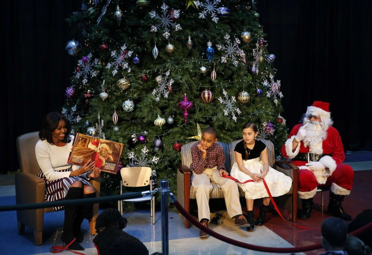 "U.S. first lady Michelle Obama (L) reads ""Twas the Night Before Christmas"" during her annual visit at the Children's National Health System in Washington December 15, 2014. Patients Aaron Kirby (C) and Kyra DeStefano (2nd R) listen with Santa Claus. (Gary Cameron/Reuters)"
