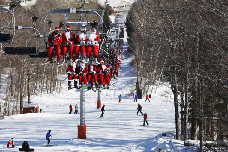 Skiers and snowboarders dressed as Santa Claus ride the chair lift to participate in a charity run down a slope at Sunday River Ski Resort in Newry, Maine December 7, 2014. Organizers say 250 skiing Santas raised $2700 for charity at the event. (Brian Snyder/Reuters)