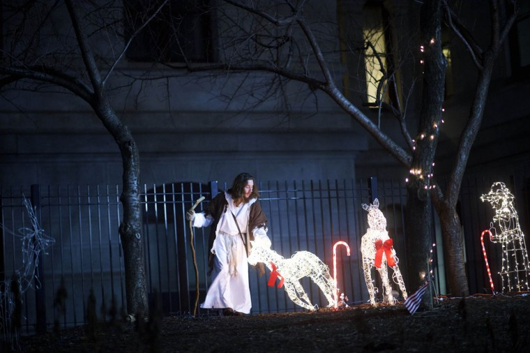 "Michael Grant, 28, ""Philly Jesus,"" lifts a fallen Christmas decoration in the courtyard of Philadelphia City Hall in Philadelphia, Pennsylvania December 14, 2014. (Mark Makela/Reuters)"