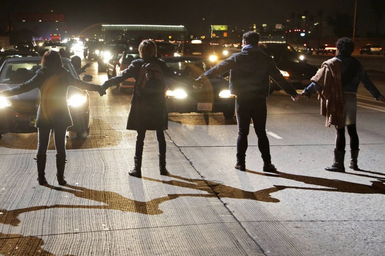 Protesters block the southbound lanes of the 110 freeway after the Los Angeles County Coroner released an autopsy report on the LAPD's shooting of Ezell Ford in Los Angeles, California December 29, 2014. Ford, an unarmed 25-year-old black man slain by Los Angeles police officers in August suffered three gunshot wounds, including one to his back, a long-awaited autopsy report into the killing showed on Monday. Police have said two officers shot Ford, described by a family lawyer as mentally challenged, on Aug. 11 after he struggled with one of them and tried to grab the officer's holstered gun. (Jonathan Alcorn/Reuters)