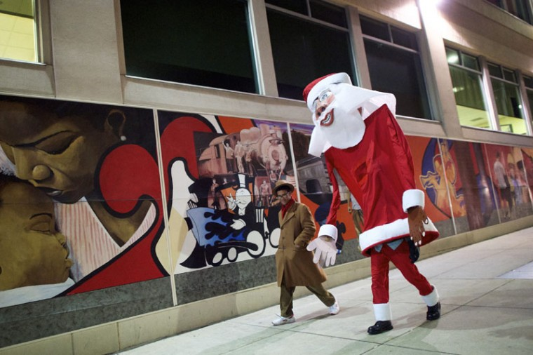 "A giant Santa Claus, created and worn by local artist Ed Terrell, 66, walks home with his son and assistant, Rupanuga, 18, following a ceremony to decorate a scraggly Christmas tree with a single red Bulb in Reading, Pennsylvania, December 7, 2014. A ceremony to decorate the scraggly Christmas tree in Reading, Pennsylvania with a single red bulb, much like Charlie Brown's tree in the animated holiday classic, was postponed to Sunday from Saturday because of rain and cold temperatures, officials said. Officials decided to hold a re-dedication ceremony, which will include a Spanish and English reading from the movie's screenplay, and decorate it with a single red bulb, as in the 1965 animated television special, ""A Charlie Brown Christmas."" (Mark Makela/Reuters)"