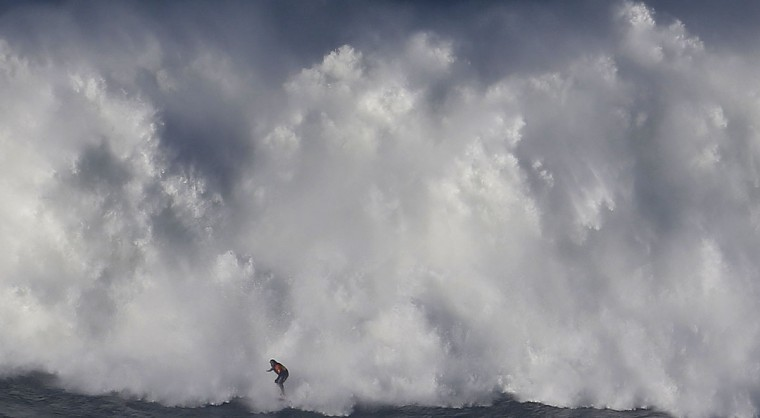 A surfer drops in on a large wave at Praia do Norte, in Nazare December 11, 2014. Praia do Norte beach has gained popularity with big wave surfers since Hawaiian surfer Garrett McNamara broke a world record for the largest wave surfed here in 2011. (REUTERS/Rafael Marchante)
