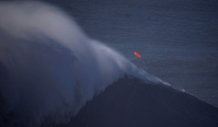 A surf board is seen on the air after a surfer failed to ride on a large wave at Praia do Norte, in Nazare December 11, 2014. Praia do Norte beach has gained popularity with big wave surfers since Hawaiian surfer Garrett McNamara broke a world record for the largest wave surfed here in 2011. (REUTERS/Rafael Marchante)