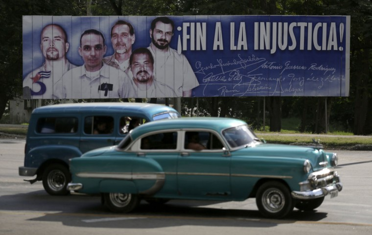"Cars drive past a banner featuring five Cuban prisoners held in U.S. custody, two of whom were previously released, in Havana December 17, 2014. U.S. President Barack Obama was set to announce a shift in policy toward Cuba on Wednesday and the Associated Press reported the changes would include the opening of an embassy in Cuba and the start of talks to normalize relations. The shift in policy, which could be one of the biggest changes in decades of animosity between communist-ruled Cuba and the United States, was heralded by Cuba's release of American aid worker Alan Gross after five years in prison in a reported prisoner exchange with Havana. CNN reported a prisoner exchange that also included Cuba's release of a U.S. intelligence source and the U.S. release of three Cuban intelligence agents. The banner reads, ""end of injustice!"". REUTERS/Enrique De La Osa"