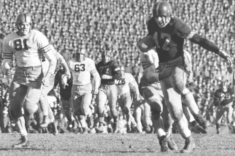 Navy's Scott catches a pass from Hamburg for a 7-yard gain in the 3rd quarter. (UM Libraries, Special Collections, News American Photo)