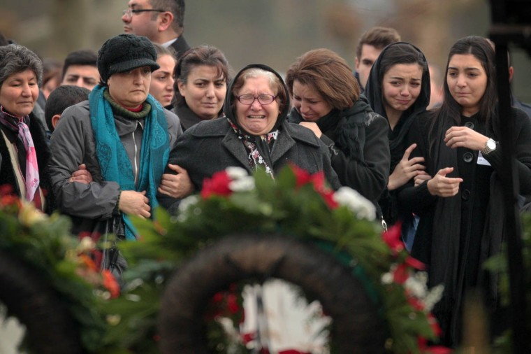 Mourners cry as they stand in front of the grave of Tugce Albayrak during her burial on December 3, 2014 at the cemetery in Bad Soden-Salmünster, western Germany. Hundreds of mourners attended the burial in Bad Soden-Salmünster and the funeral service in Waechtersbach for the young woman of Turkish origin who was attacked and later died after confronting a male group harrassing two teenage girls, sparking public outrage. (Fredrik Von Erichsen/Getty Images)