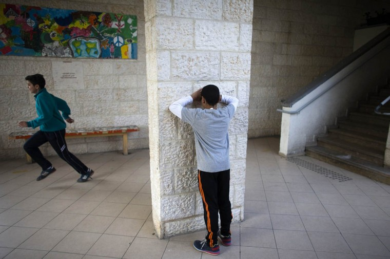 Children play hide-and-seek during lunch break at the Hand in Hand Arab Jewish bilingual school in Jerusalem December 3, 2014. The Hand in Hand school in Jerusalem presents an almost too-perfect scene in a tense and divided city, where Jews and Arabs do daily business but rarely befriend one other. (Ronen Zvulun/Reuters photo)
