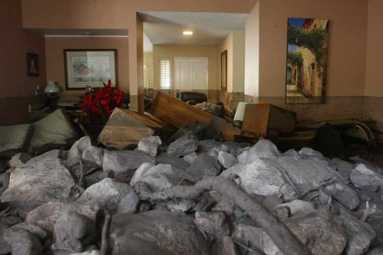 A home is filled with rocks and mud after debris flows smashed into homes as a powerful storm that has been lashing northern California moves southward on December 12, 2014 in Camarillo Springs neighborhood of Camarilla, California. About two dozen homes were severely damage in a heavy pre-dawn downpour. Although water from the storm lowers the risk of wildfires and offers some short-term relief from the record drought conditions that are menacing the state, weather experts say it amounts to only a very small step toward ending the drought. (David McNew/Getty Images)