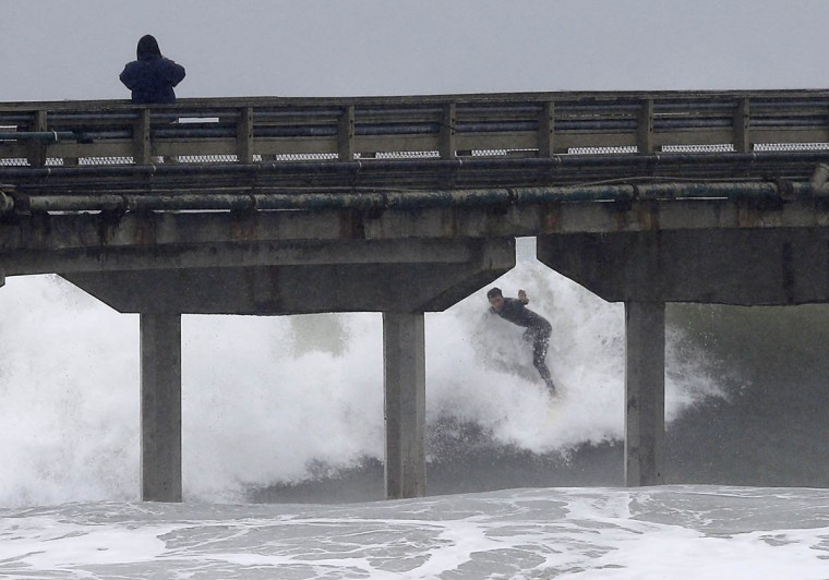 A surfer catches a wave next to the Ocean Beach Pier as a winter storm brings high surf, rain and wind to San Diego, California December 12, 2014. (Mike Blake/Reuters photo)
