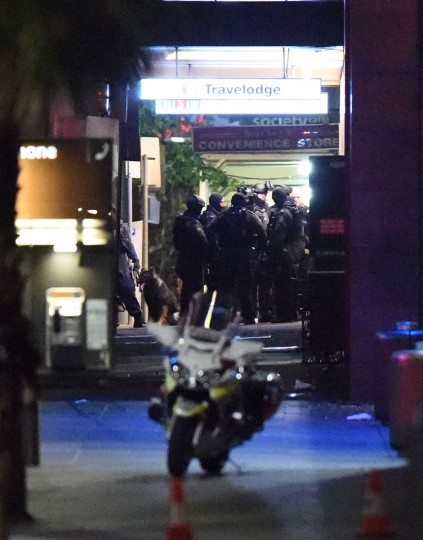Armed police carry out an operation outside the cafe where a gunman had taken people captive in the central business district of Sydney on December 15, 2014. (SAEED KHAN/AFP/Getty Images)
