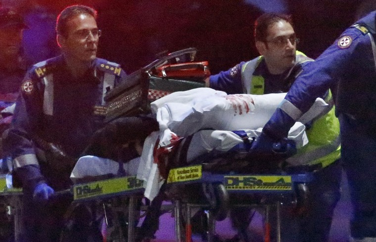 Paramedics remove a person, with bloodstains on the blankets covering the person, on a stretcher from the Lindt cafe, where hostages were being held, at Martin Place in central Sydney December 16, 2014. (REUTERS/David Gray)