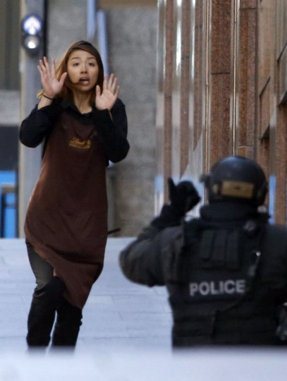 A hostage runs towards a police officer outside Lindt cafe, where other hostages are being held, in Martin Place in central Sydney December 15, 2014. (REUTERS/Jason Reed)