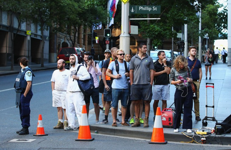 Onlookers are seen just outside the exclusion zone around Philip and Hunter Streets on December 15, 2014 in Sydney, Australia. (Photo by Don Arnold/Getty Images)