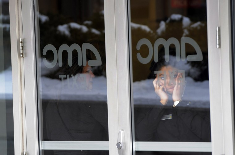 A Sprint employee waits inside the lobby of the AMC theater at The Mall in Columbia Saturday afternoon. Many people who were working or shopping at the mall were moved there following a shooting on an upper level of the mall where three people were killed. (Kim Hairston/Baltimore Sun)