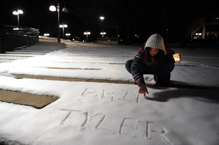 Nisa Pereira, 19, writes the names of mall shooting victims Tyler Johnson and Brianna Benlolo in the snow during a vigil on Sunday January 26, 2014 in Columbia. (Washington Post photo by Matt McClain)