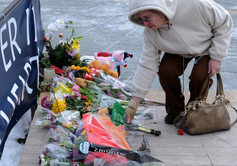 Theresa Olson from Columbia places flowers on the memorial in the plaza outside The Mall in Columbia whichreopened at 1pm today after the weekend shootings in which three people died including the Darion Marcus Aguilar, 19, who shot two victims. Photo by Algerina Perna/Baltimore Sun}