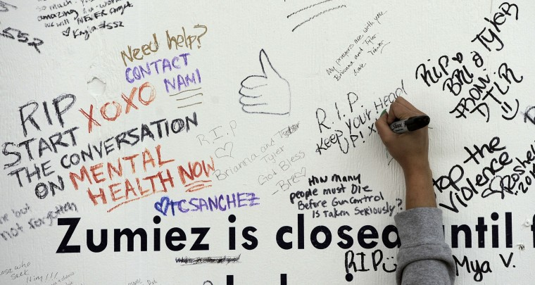 Kaila Hall, Ellicott CIty, president of the Howard County NAACP Youth Council, writes a message on the boarded up Zumiez store in The Mall in Columbia on the one week anniversary of the mall shooting of Zumiez employees Brianna Benlolo and Tyler Johnson. (Kim Hairston/Baltimore Sun Staff. )