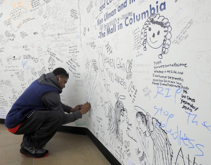 "Drew ""DJ"" Gordon, Columbia, writes a message on the boarded up Zumiez store in The Mall in Columbia on the one week anniversary of the mall shooting of Zumiez employees Brianna Benlolo and Tyler Johnson. (Kim Hairston/Baltimore Sun Staff.)"