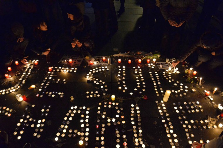 People gather around candles and pens at the Place de la Republique (Republic square) in support of the victims after the terrorist attack earlier today on January 7, 2015 in Paris, France. Twelve people were killed, including two police officers, as two gunmen opened fire at the offices of the French satirical publication Charlie Hebdo. (Aurelien Meunier/Getty Images)