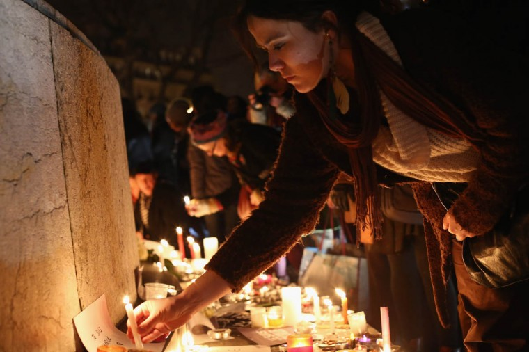 A woman places a candle at a vigil at the Place de la Republique (Republic Square) for victims of the terrorist attack, on January 7, 2015 in Paris, France. Twelve people were killed, including two police officers, after gunmen opened fire at the offices of the French satirical publication Charlie Hebdo. (Dan Kitwood/Getty Images)