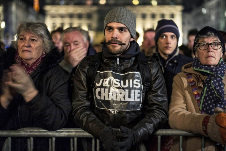 "A man with a logo on his jacket that reads in French, ""I am Charlie"" and a pen in his mouth, stands with other during a rally in Lyon, on January 7, 2015, following an attack by unknown gunmen on the offices of the satirical weekly, Charlie Hebdo. France's Muslim leadership sharply condemned the shooting at the Paris satirical weekly that left at least 12 people dead as a ""barbaric"" attack and an assault on press freedom and democracy. (Jeff Pachoud/AFP/Getty Images)"
